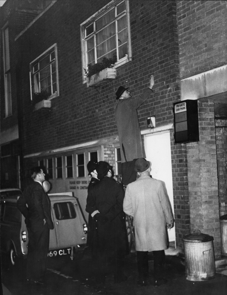 Detectives scrutinising the bullet holes at Stephen Ward's flat after the shooting incident, December 1962 (© Rex Features).